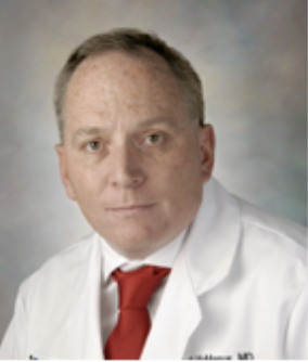 Headshot of Dr. John McManus in white coat and red tie.