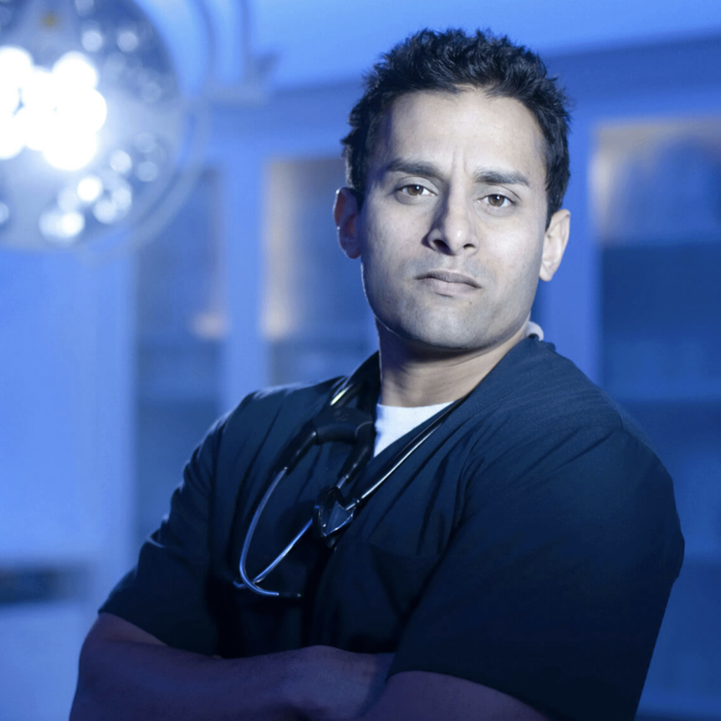 Headshot of Dr. Sudip Bose in surgical theater wearing dark blue scrubs and stethoscope around his neck.